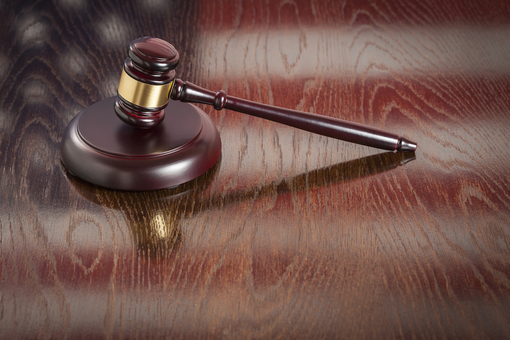 Wooden Gavel Resting on Table Reflecting American Flag.