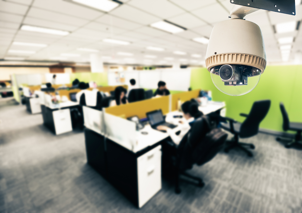 surveillance camera operating in office with employees at desks