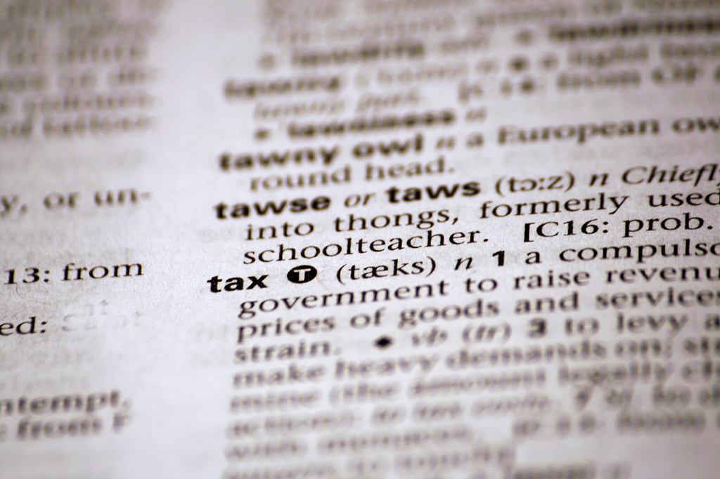 photo of a dictionary page with the word tax and part of its definition in focus.